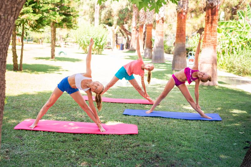 Beautiful young girls working out, exercising outdoor. Beautiful young girls working out, exercising, practicing yoga outdoor at the resort. Healthy lifestyle royalty free stock images