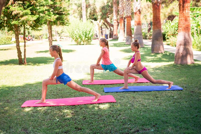 Beautiful young girls working out, exercising outdoor. Beautiful young girls working out, exercising, practicing yoga outdoor at the resort. Healthy lifestyle royalty free stock photos