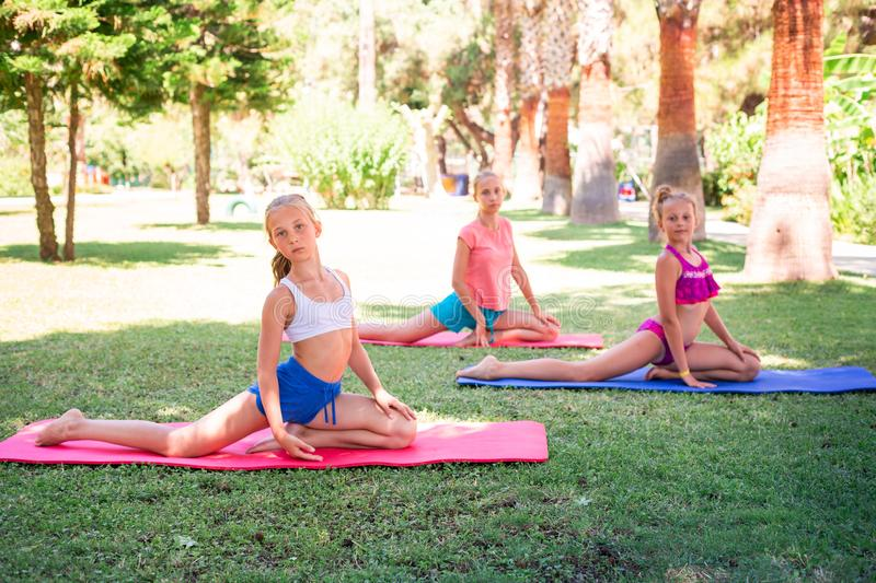 Beautiful young girls working out, exercising outdoor. Beautiful young girls working out, exercising, practicing yoga outdoor at the resort. Healthy lifestyle royalty free stock photography