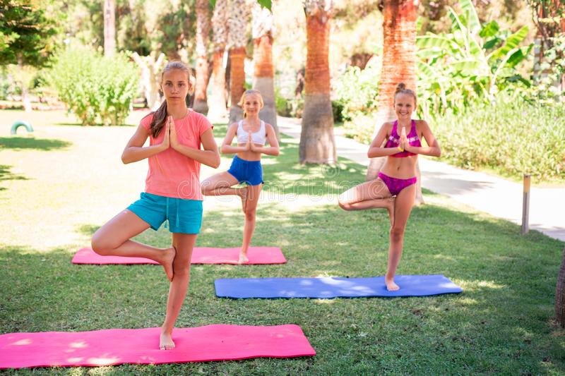 Beautiful young girls working out, exercising outdoor. Beautiful young girls working out, exercising, practicing yoga outdoor at the resort. Healthy lifestyle stock photos