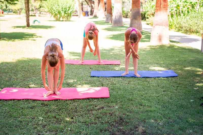 Beautiful young girls working out, exercising outdoor. Beautiful young girls working out, exercising, practicing yoga outdoor at the resort. Healthy lifestyle stock image