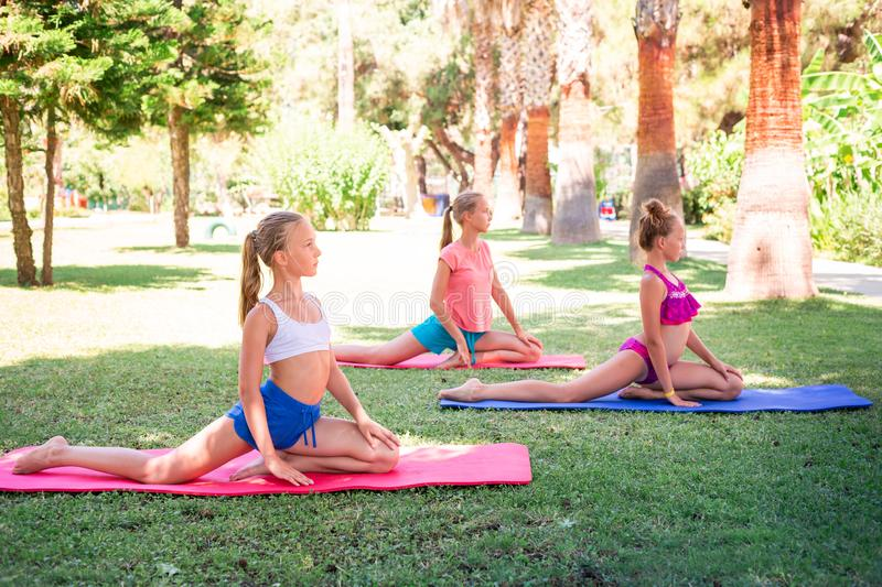 Beautiful young girls working out, exercising outdoor. Beautiful young girls working out, exercising, practicing yoga outdoor at the resort. Healthy lifestyle stock photography