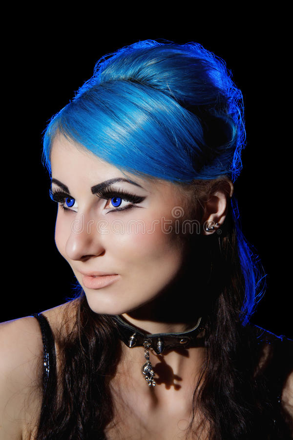 Beautiful young gothic woman with blue hairs. Portrait of beautiful gothic woman with blue hairs and bright makeup, isolated on black background stock image