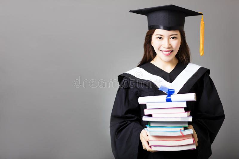 Beautiful young graduate holding diploma and book stock photography