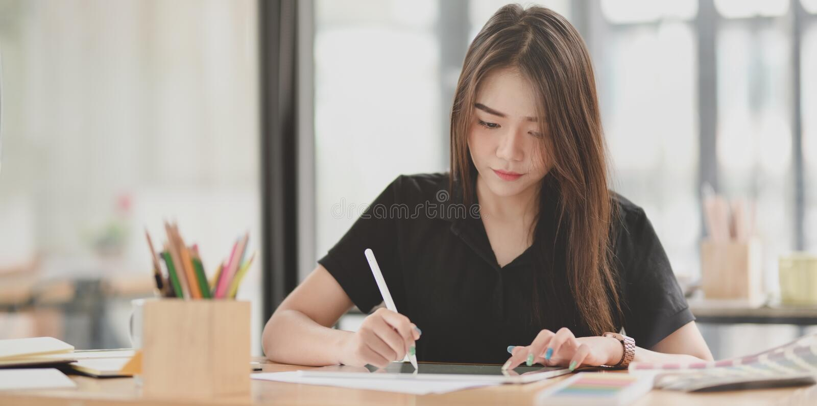 Beautiful young graphic designer working on her project stock photography
