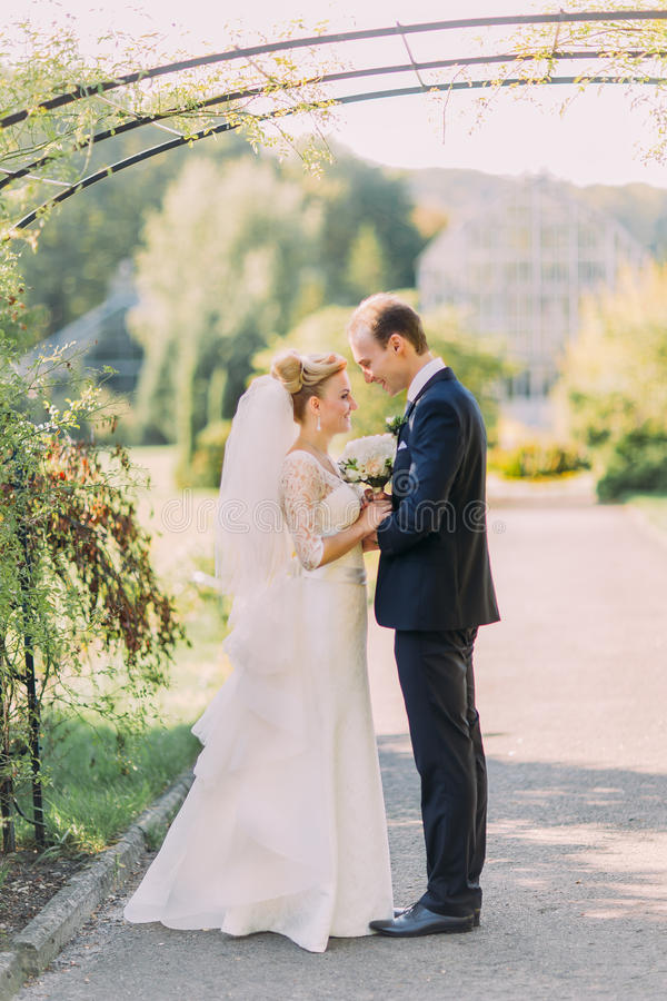 Beautiful young groom and bride looking each other at wedding day. Sunny summer park on background royalty free stock photo