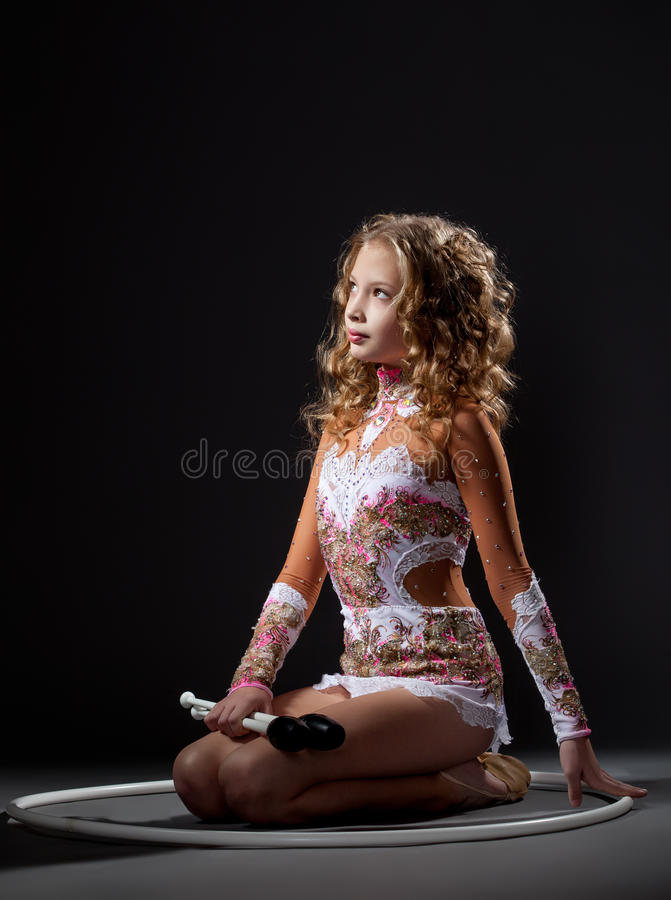 Beautiful young gymnast posing with mace and hoop stock photo