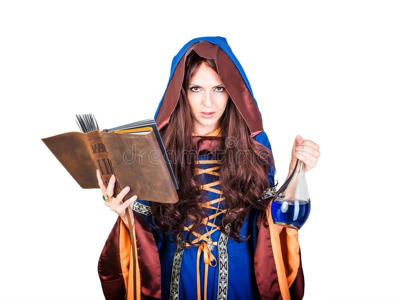 Beautiful young halloween witch reading magical book and holding stock image