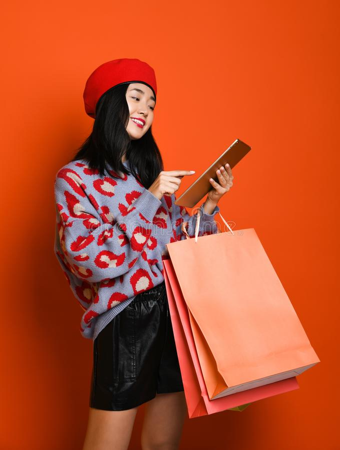 Woman holding shopping bag and using tablet for shopping online, shopping concept. Beautiful young happy Asian woman in a stylish beret and sweater, with a stock image