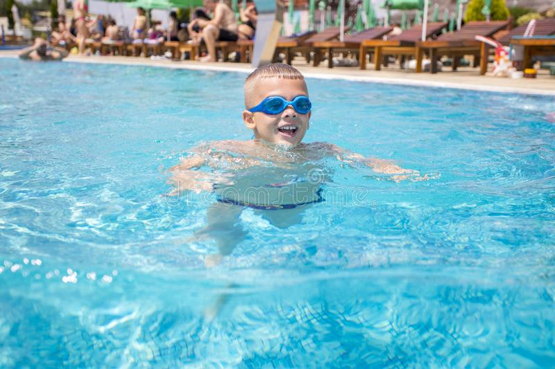 Beautiful young happy boy swimming in a swimming pool royalty free stock photo