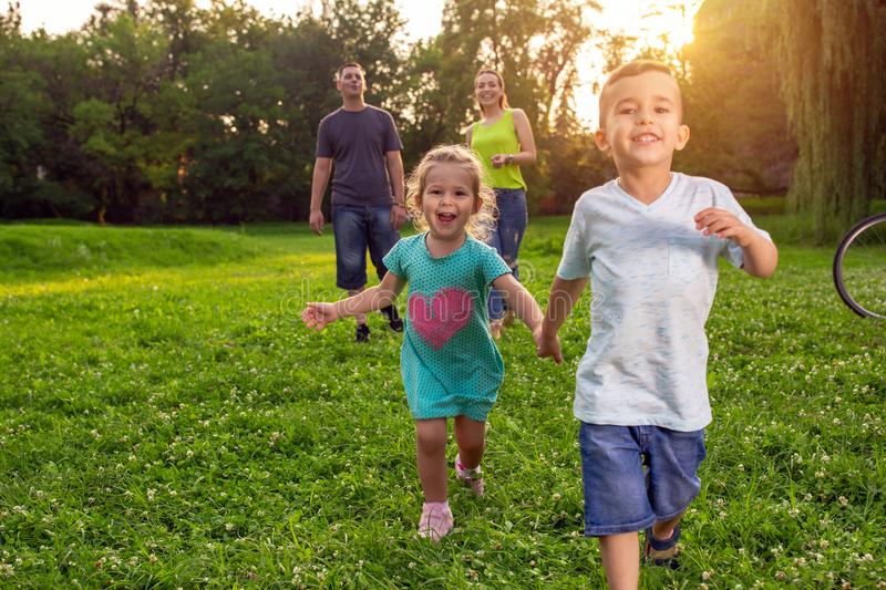 Beautiful happy children walking with parents in park stock images