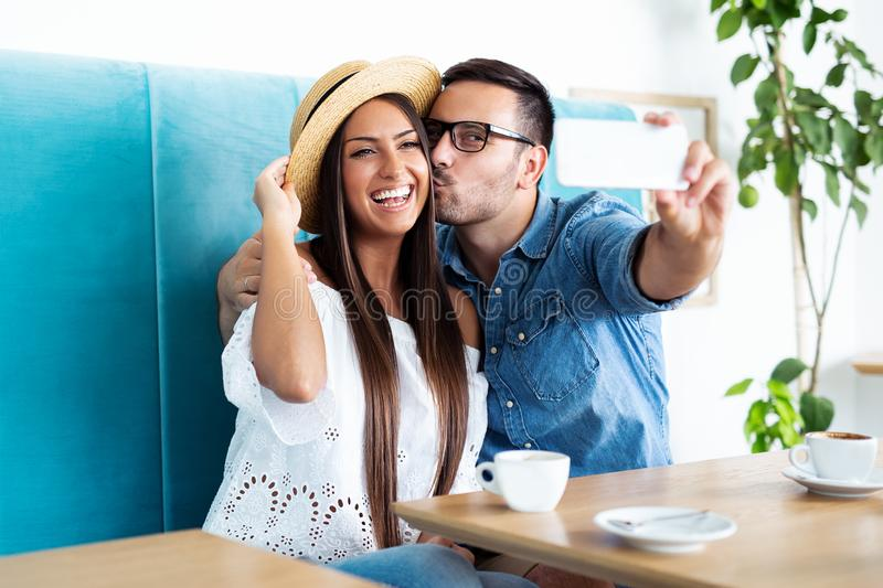Young happy couple doing selfie in a cafe royalty free stock image