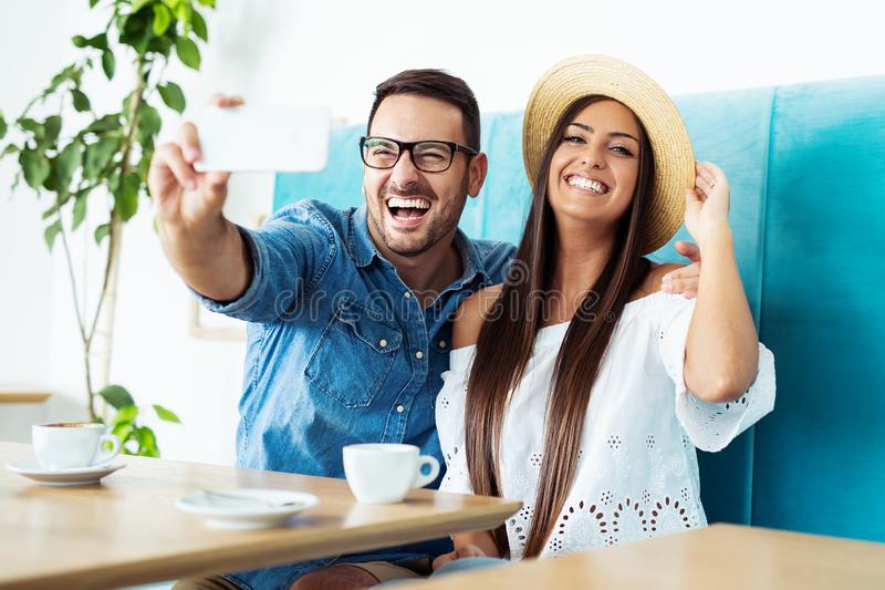 Young happy couple doing selfie in a cafe stock photography