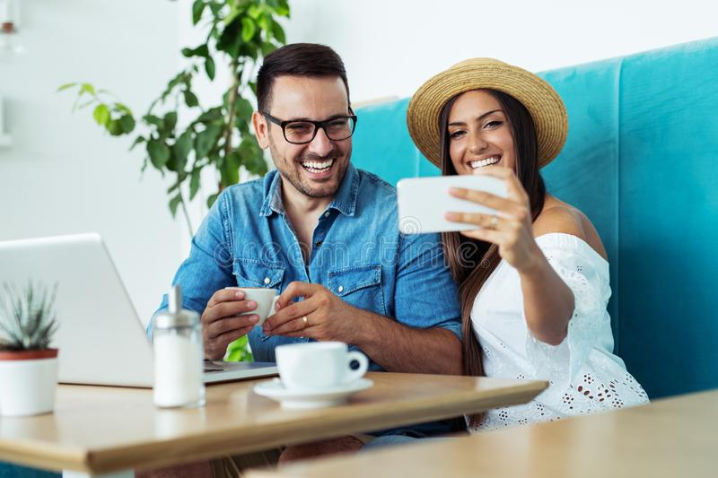 Young happy couple doing selfie in a cafe royalty free stock photos