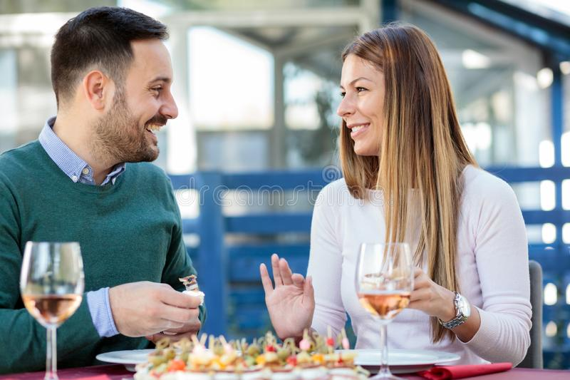Beautiful young happy couple enjoying lunch and wine in outdoor restaurant royalty free stock image