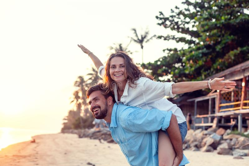 Beautiful young happy couple in love having fun on the beach at sunset during the honeymoon vacation travel, the guy carries the stock images