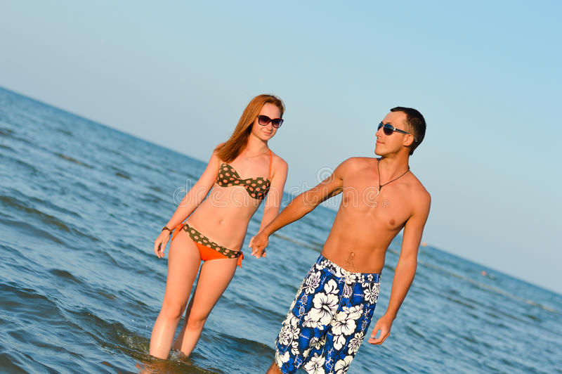Beautiful young happy couple walking holding hands on seashore stock images