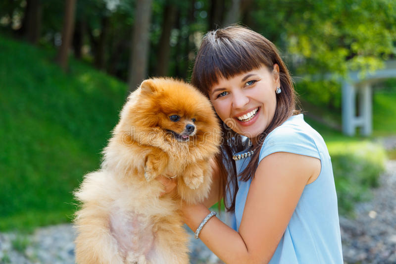 Beautiful young happy girl with Spitz royalty free stock photo