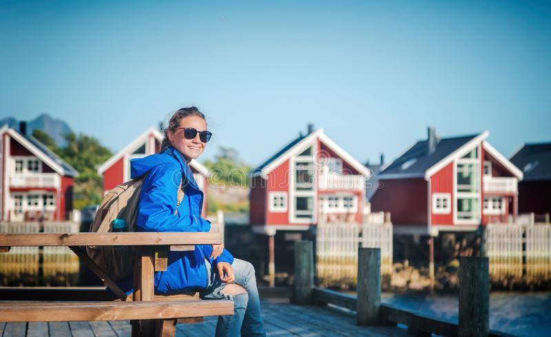 Beautiful young happy smiling girl traveler on the background of traditional red rorbu traveling to Lofoten Norway stock photo