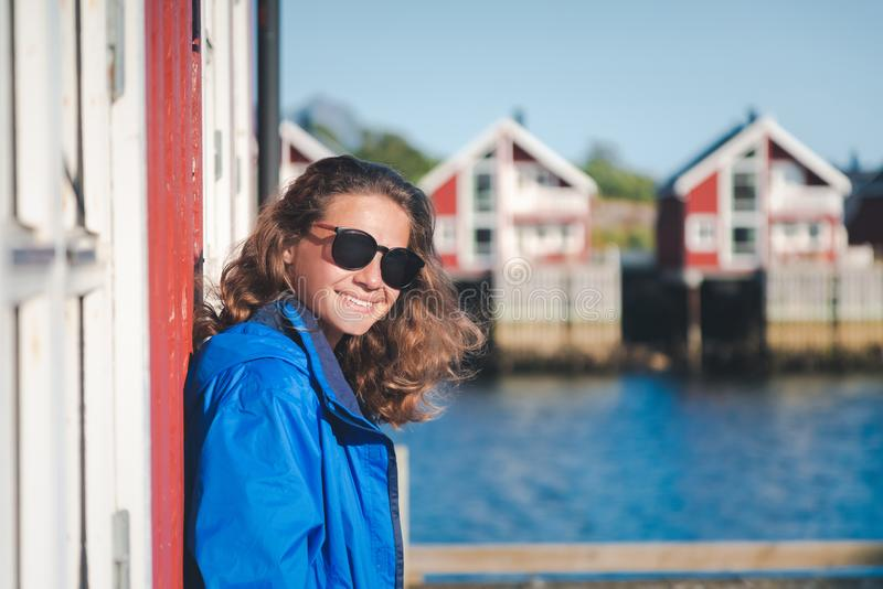 Beautiful young happy smiling girl traveler on the background of traditional red rorbu traveling to Lofoten Norway stock image