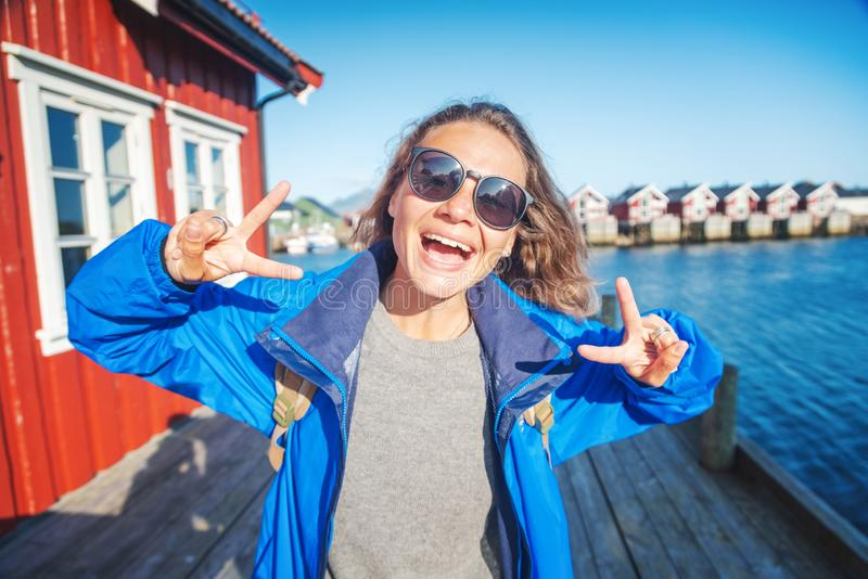 Beautiful young happy smiling girl traveler on the background of traditional red rorbu traveling to Lofoten Norway royalty free stock images