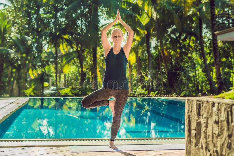 Beautiful young happy woman doing yoga exercise near swimming pool. Healthy lifestyle and good wellness concepts royalty free stock images