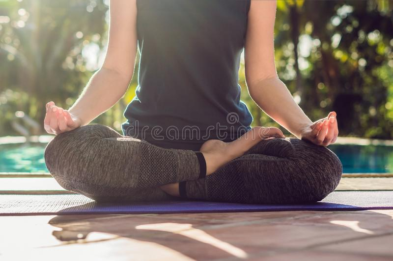 Beautiful young happy woman doing yoga exercise near swimming pool. Healthy lifestyle and good wellness concepts.  stock photography