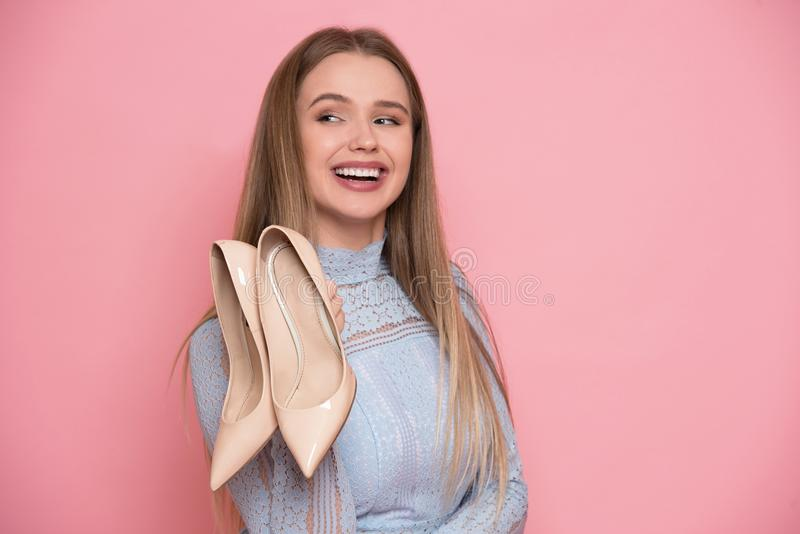 Beautiful young happy woman holding high heels shoes. Female shopping concept. royalty free stock image