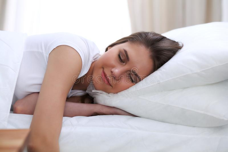 Beautiful young and happy woman sleeping while lying in bed comfortably and blissfully smiling.  royalty free stock image