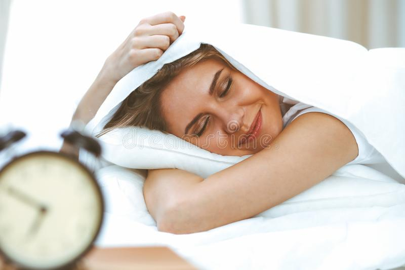 Beautiful young and happy woman sleeping while lying in bed comfortably and blissfully smiling.  stock image