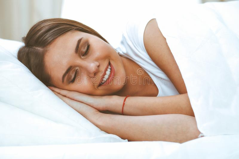 Beautiful young and happy woman sleeping while lying in bed comfortably and blissfully smiling.  royalty free stock photo