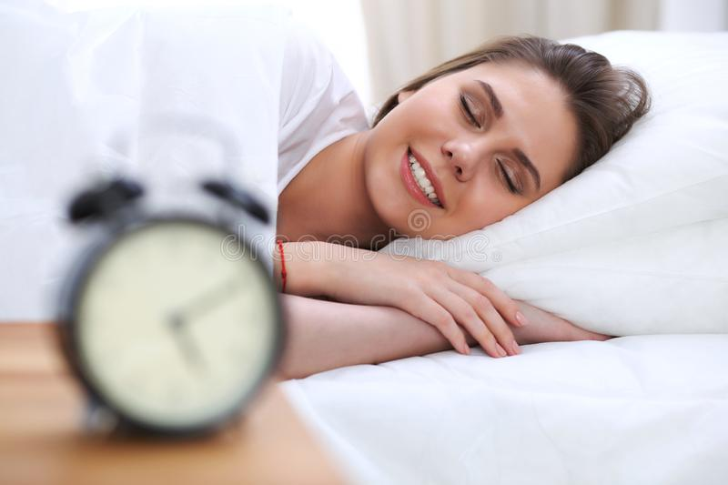 Beautiful young and happy woman sleeping while lying in bed comfortably and blissfully smiling.  stock photos