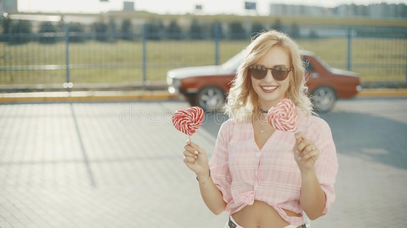 Beautiful young happy woman on the street with two colored lollipop at sunset stock photos