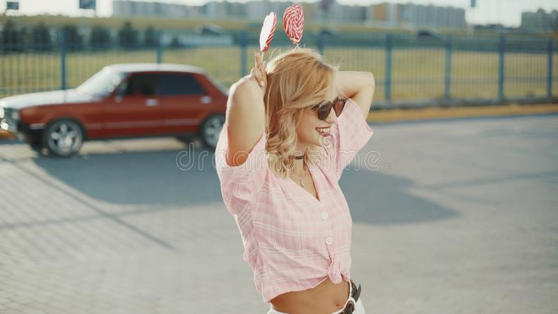 Beautiful young happy woman on the street with two colored lollipop at sunset stock image