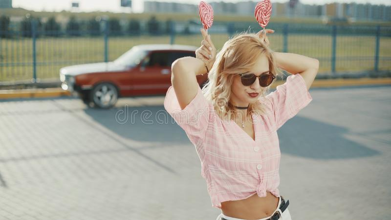 Beautiful young happy woman on the street with two colored lollipop at sunset royalty free stock photos