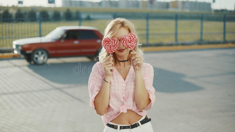Beautiful young happy woman on the street with two colored lollipop at sunset royalty free stock photo