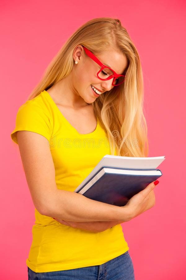 Beautiful young happy woman in yellow t shirt holds folder pose stock image