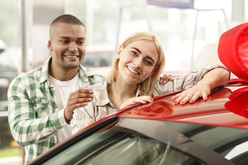 Happy couple buying new car together at the dealership. Beautiful young happy women smiling to the camera, posing near new automobile, her loving husband buying royalty free stock photo