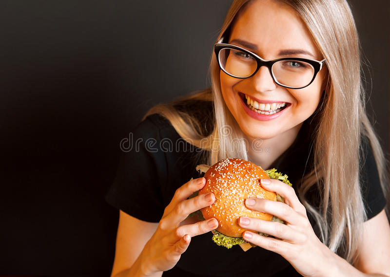 Beautiful young, healthy girl holds a tasty big burge. R with beef cutlet. the concept of nourishing food royalty free stock photos