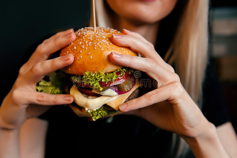 Beautiful young, healthy girl holds a tasty big burger with beef cutlet stock photo