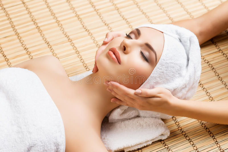 Beautiful, young and healthy woman on bamboo mat in spa salon having face massage. royalty free stock images