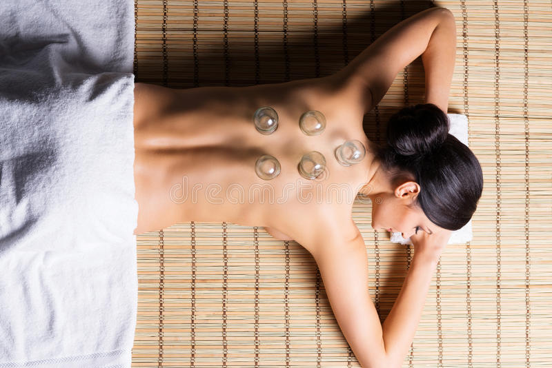 Beautiful, young and healthy woman on bamboo mat in spa salon is having vacuum cupping. royalty free stock photos