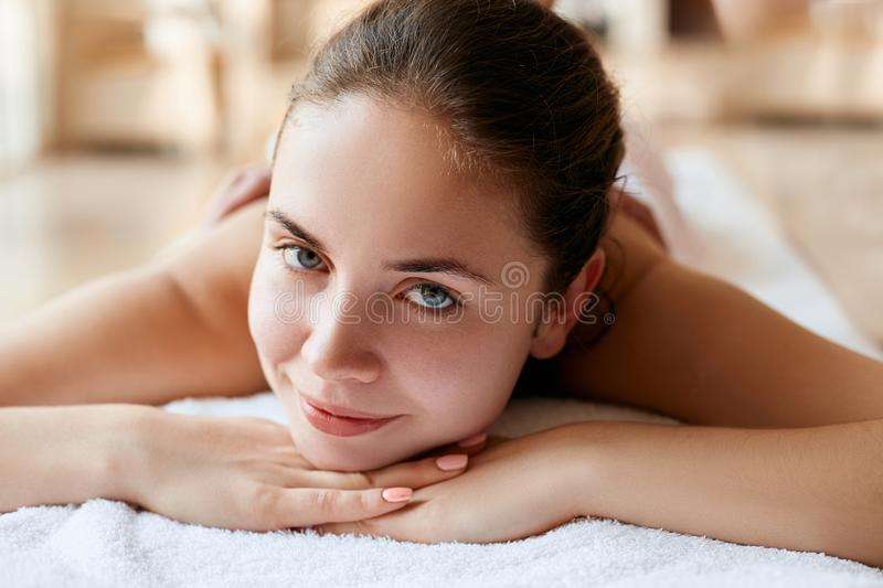 Beautiful, young and healthy woman in spa salon. Spa, health and healing concept. Massage treatment royalty free stock images