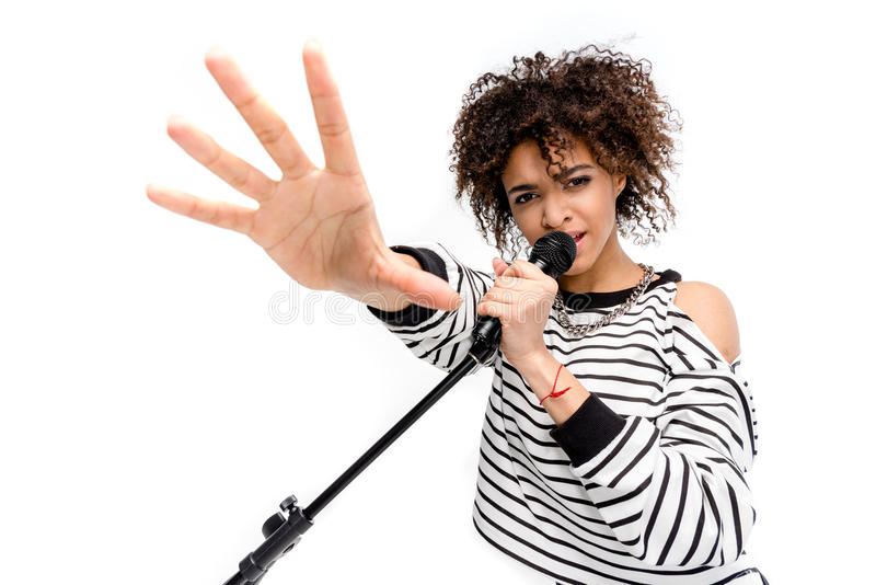 Beautiful young heavy metal singer with microphone singing and gesturing royalty free stock images