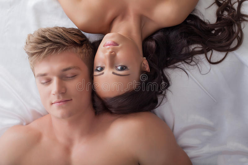 Beautiful young heterosexual couple in bed stock images