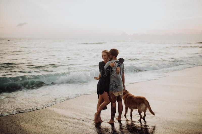 Beautiful happy laugh young hipster couple with golden retriever on beach. ocean an sand. waves. concepte of freedom and royalty free stock images