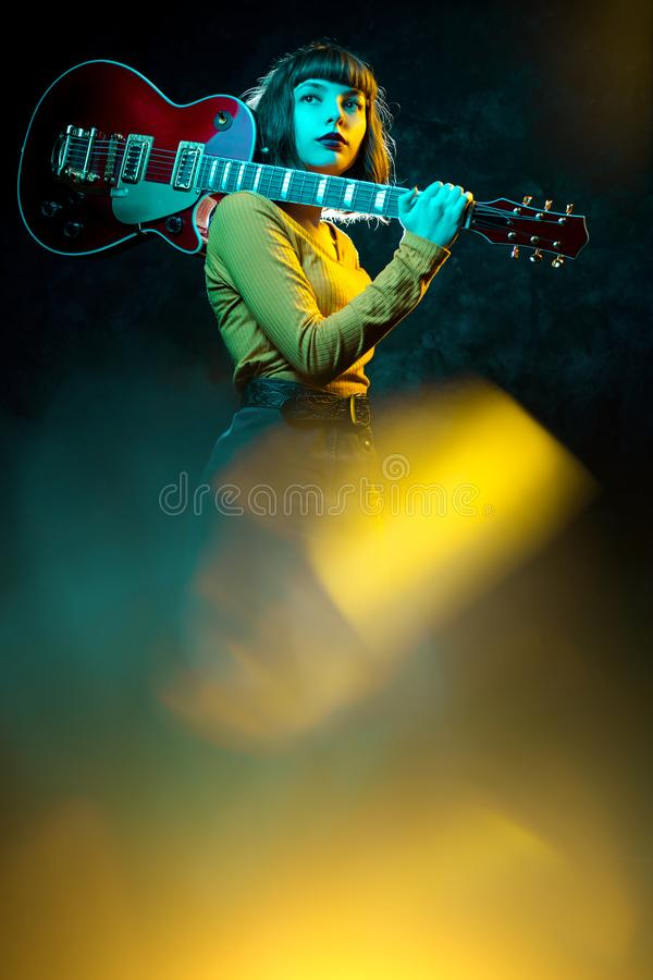 Beautiful young hipster woman with curly hair with red guitar in neon lights. Rock musician is playing electrical guitar. 90s style concept stock photo