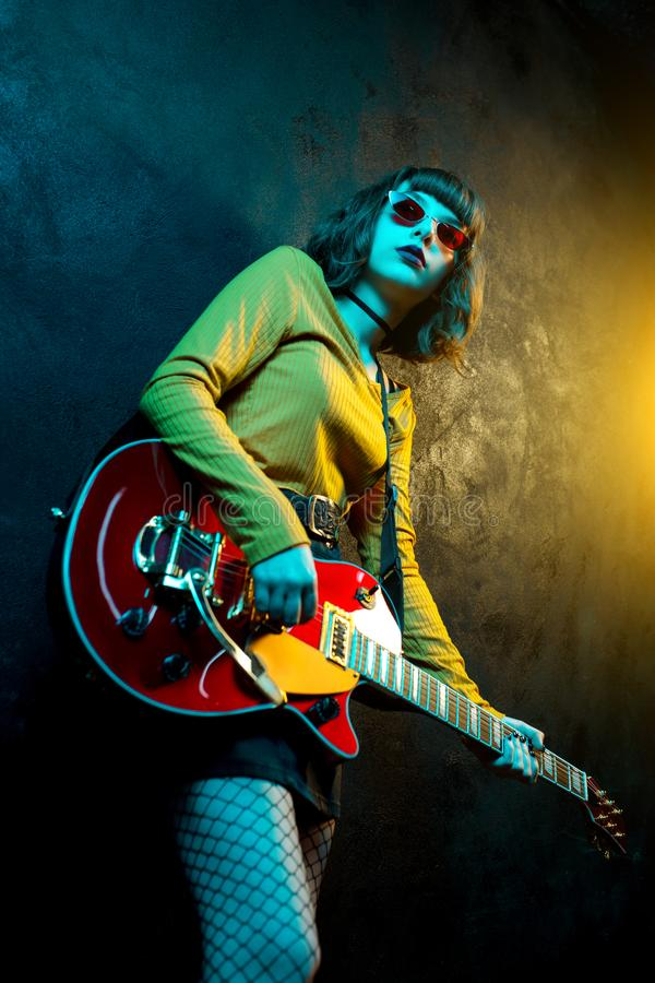 Beautiful young hipster woman with curly hair with red guitar in neon lights. Rock musician is playing electrical guitar. 90s style concept royalty free stock photo