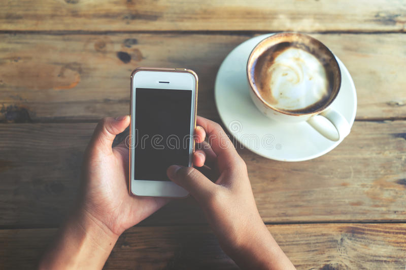 Beautiful young hipster woman`s hands holding mobile smart phone with hot coffee cup at cafe shop, stock photos