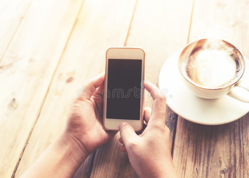 beautiful young hipster woman`s hands holding mobile smart phone with hot coffee cup at cafe shop royalty free stock images